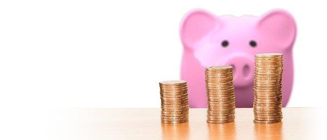 Sparschweinchen, das sehnsüchtig auf einige aufgestapelte Münzen schaut