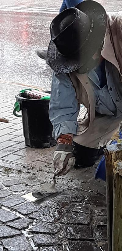 Gunter Demnig auf nasser Straße knieend beim Verlegen des Stolpersteins