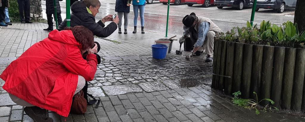 Fotografen fotografieren Gunter Demnig beim Verlegen des Stolpersteins