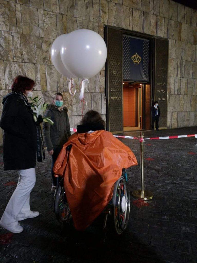 Bei Nacht vor der Synagoge. Zwei weiße Luftballons und die weißen Lilien warten auf ihren Einsatz.