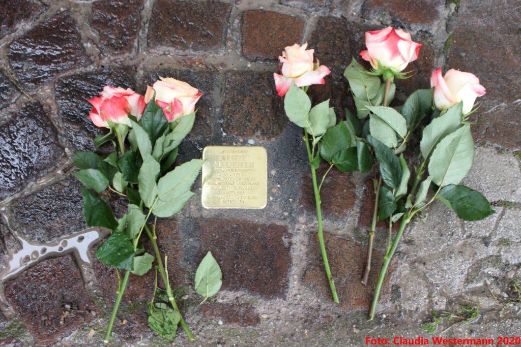 Der neu verlegte Stolperstein für Therese Mühlberger. Daneben fünf weiße Rosen mit rotem Blattrand.