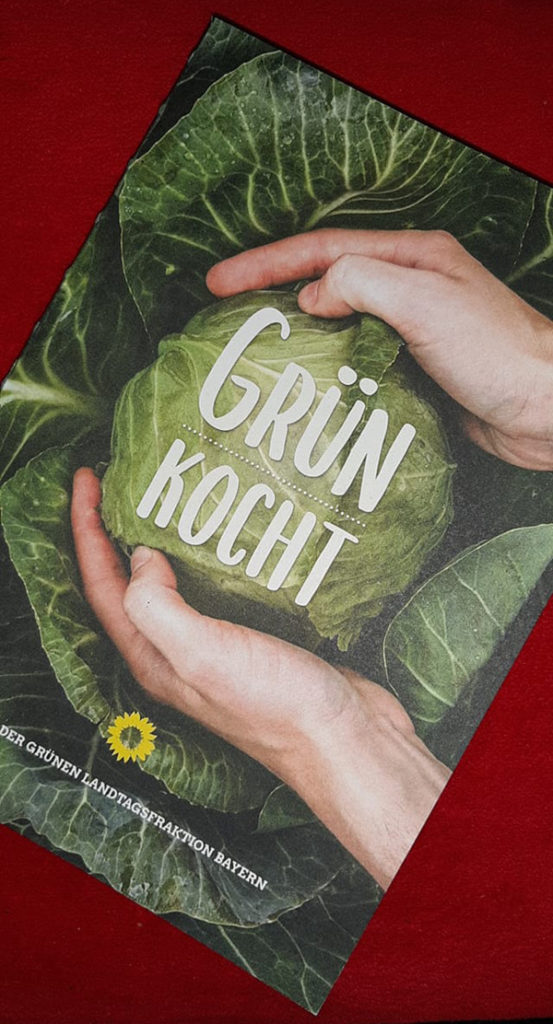 Ein Kochbuch mit dem Titel: Grün kocht.  Auf dem Cover ist ein Grünkohl zu sehen, der von zwei Händen liebevoll gehalten wird