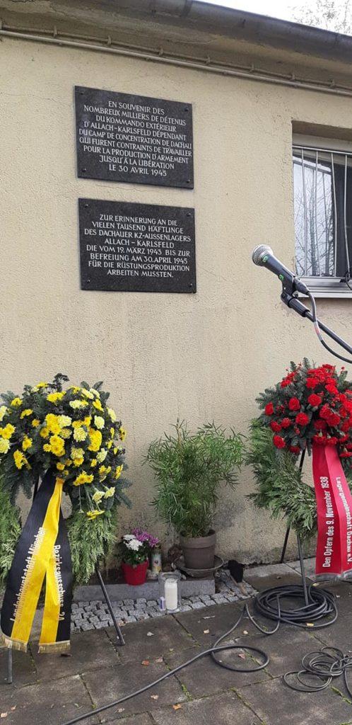 Foto vor der Veranstaltung: Blumensträuße mit Trauerschleifen vor der Baracke. Das Mikrophon steht bereit für die Redner, die einige Schicksale jüdischer Opfer verlesen werden. Auf der Inschrift am Gebäude steht:  Zur Erinnerung an die vielen tausend Häftlinge, des Dachauer KZ-Außenlagers Allach-Karlsfeld, die vom 19. März 1943 bis zur Befreiung am 30. April 1945für die Rüstungsindustrie arbeiten mußten.