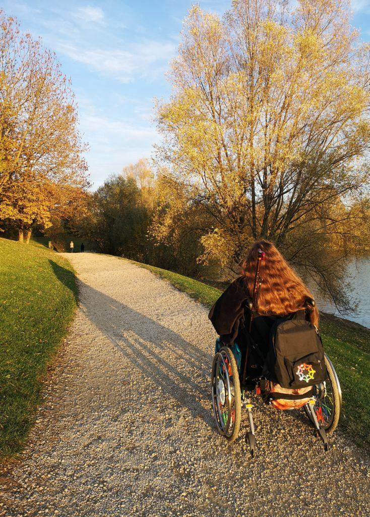 Patricia Koller im Rollstuhl auf einem herbstlichen Weg bei untergehender Sonne.