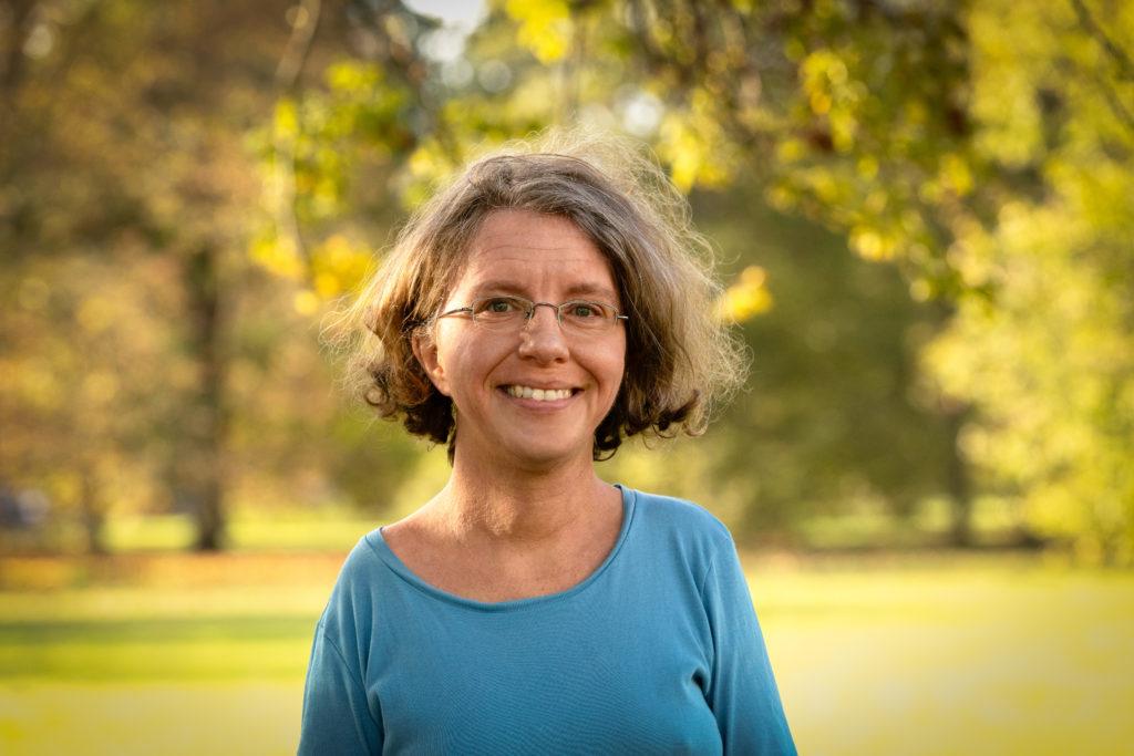 Foto von Katrin Langensiepen. Sie steht lächelnd im Grünen