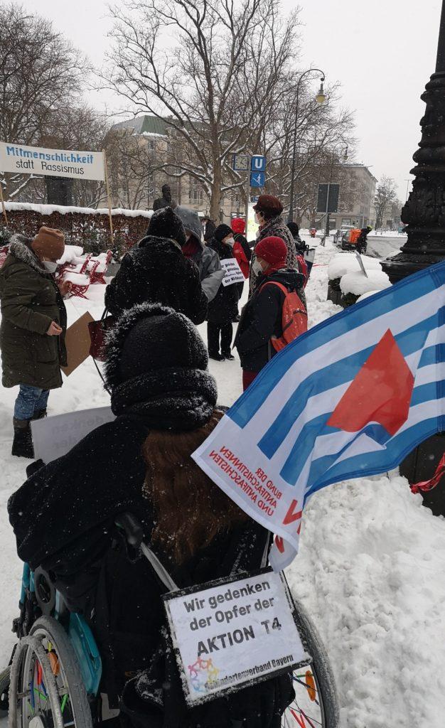 Foto von der stillen Kundgebung.Im Vordergrund die Fahne des VVN BdA und Patricia Koller im Rollstuhl mit unserem Schild zum Gedenken der Opfer der Aktion T4