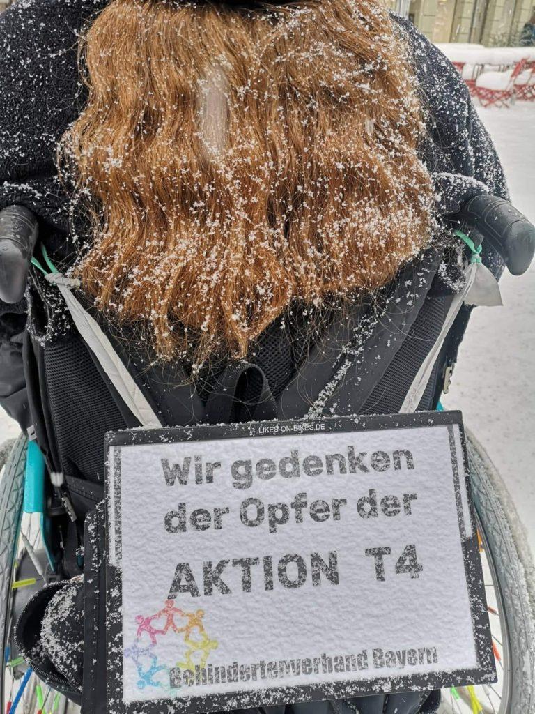 Rollstuhl von hinten mit dem Schild zum Gedenken der Opfer der Aktion T4