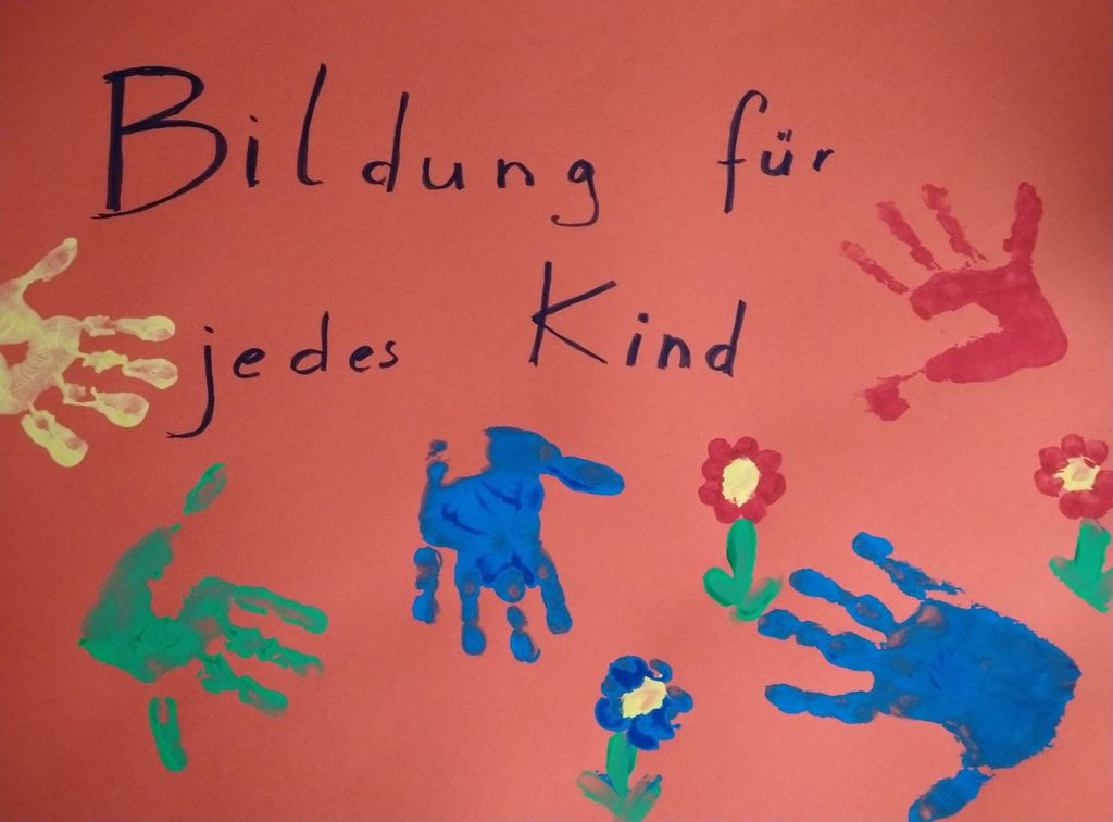 Kindliches Demoschild mit verschieden großen Händen und Blümchen. Aufschrift: Bildung für jedes Kind.