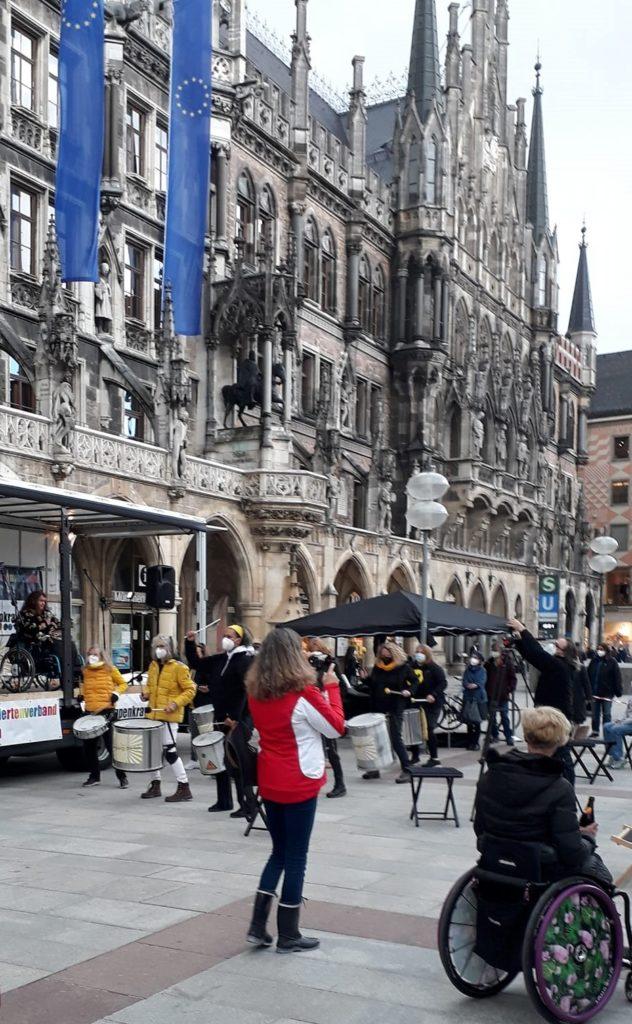 Demo auf dem Münchner Marienplatz vor dem Rathaus. Auf der Bühne Patricia Koller, davor die Trommlerinnengruppe Drumadama und  Menschen aus dem Publikum