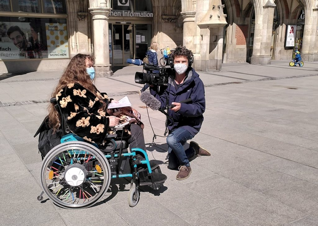 Kameramann kniet vor der im Rollstuhl sitzenden Patricia Koller