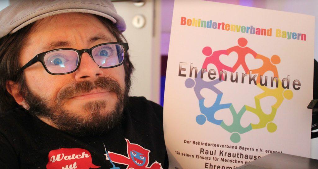 Auf dem Foto sieht man Raul Krauthausen mit seiner Ehrenurkunde vom Behindertenverband Bayern e.V.