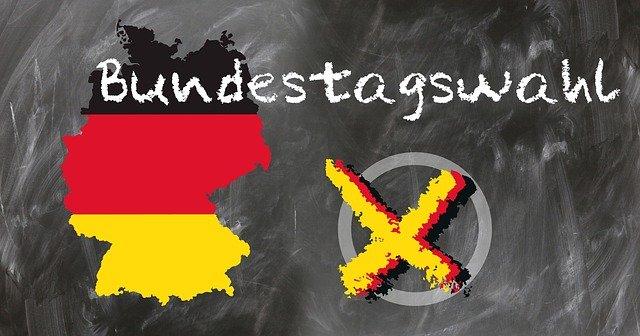 Tafel mit der Kreide-Aufschrift Bundestagswahl  Dazu ist links ein Umriss Deutschlands zu sehen und rechts ein angekreuzter Kreis