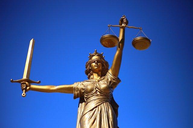 Goldene Justitia vor blauem Hintergrund