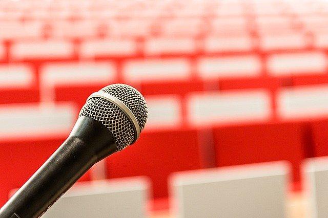 Vortragssaal. Man sieht im Vordergrund ein Mikrophon vor noch leeren Stuhlreihen