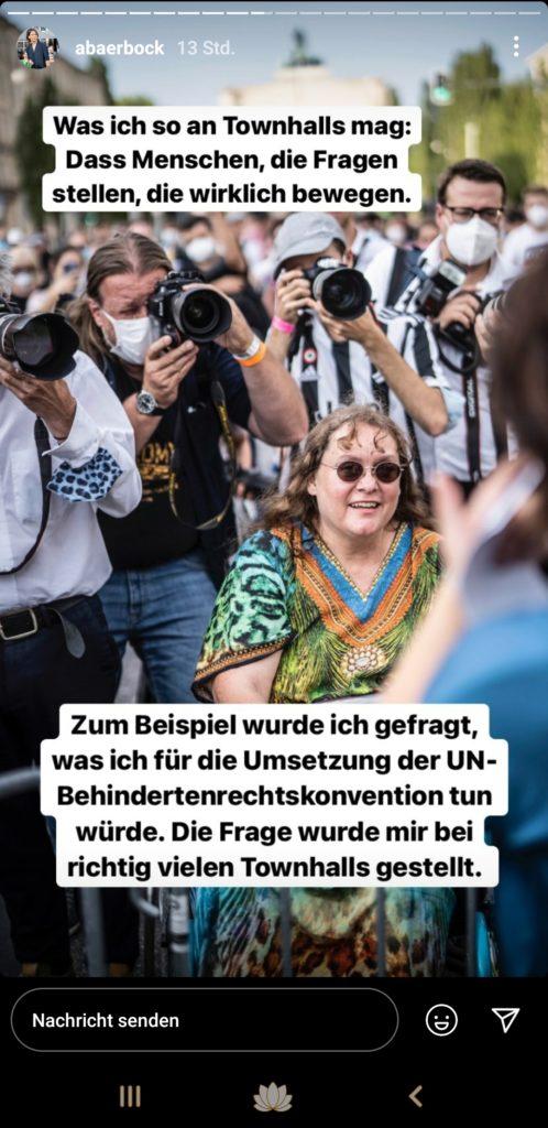 """Patricia Koller (im Rollstuhl) fragt Annalena Baerbock bei ihrem Besuch in München. Hinter ihr stehen dicht gedrängt Fotografen und dahinter schart sich eine Menschenmenge, die zu der Wahlkampfveranstaltung gekommen ist.   Annalena Baerbock schreibt dazu: """"Was ich so an Townhalls mag: Das Menschen, die Fragen stellen, die wirklich bewegen.  Zum Beispiel wurde ich gefragt, was ich für die Umsetzung der UN-Behindertenrechtskonvention tun würde. Die Frage wurde mir bei richtig vielen Townhalls gestellt. """""""